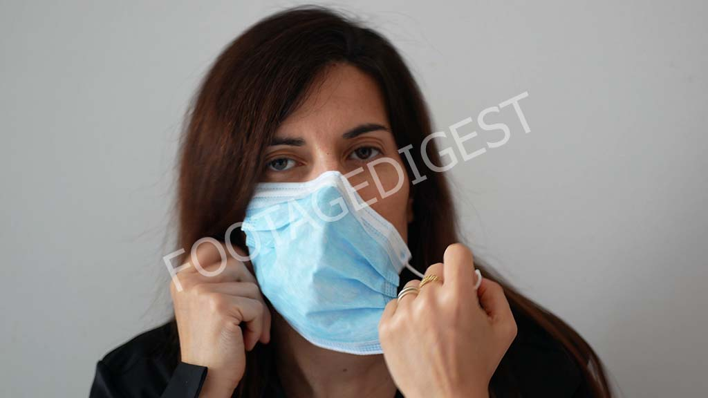 Woman takes off medical surgery face mask